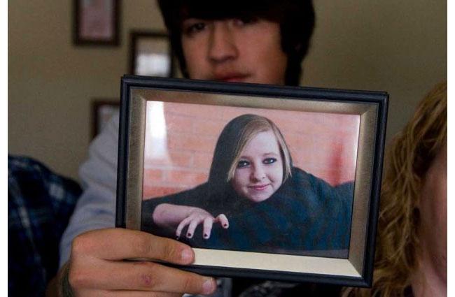 Брат Дженни Лэйк держит фотографию сестры.
